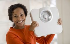 Beautiful African American woman holding scale