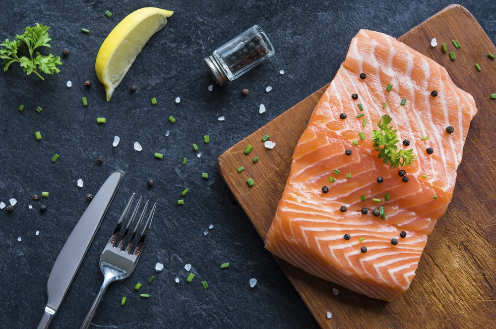 Raw salmon fillet on a wooden cutting board with lemon and citrus