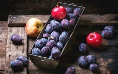 Vintage metal bowl with plums and apples over old wooden table.