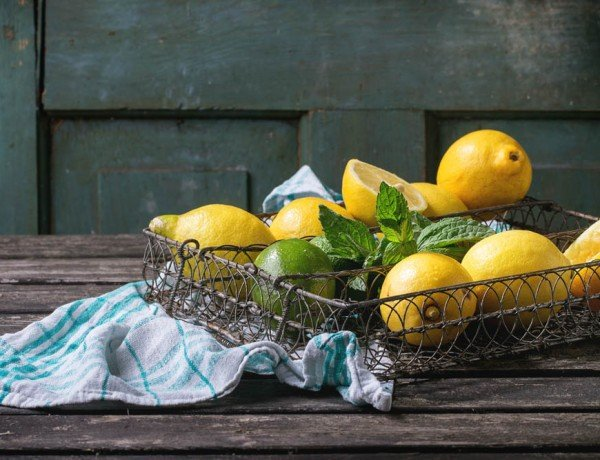 Heap of whole and sliced lemons and limes with mint in vintage metal grid box over old wooden table with turquoise wooden background. Dark rustic style.