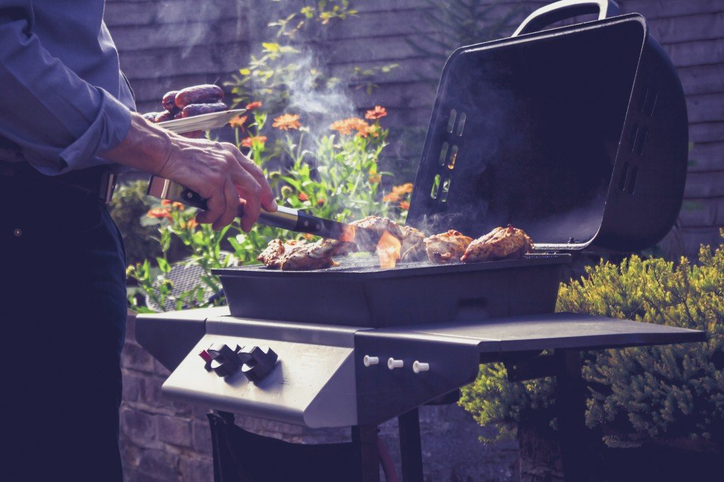 Senior man is in his garden and cooking sausages and chicken on the barbecue on a sunny day