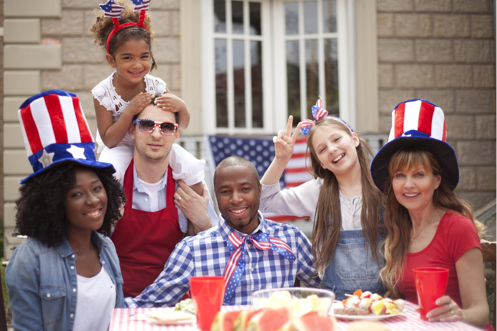 Smiling friends having fun at their back yard on4th July. .