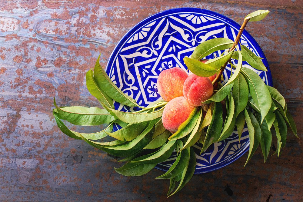 Peaches on branch with leaves on ornate blue plate over old metal background. Top view.
