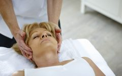 Mature woman lying on table receiving head massage from osteopath therapist