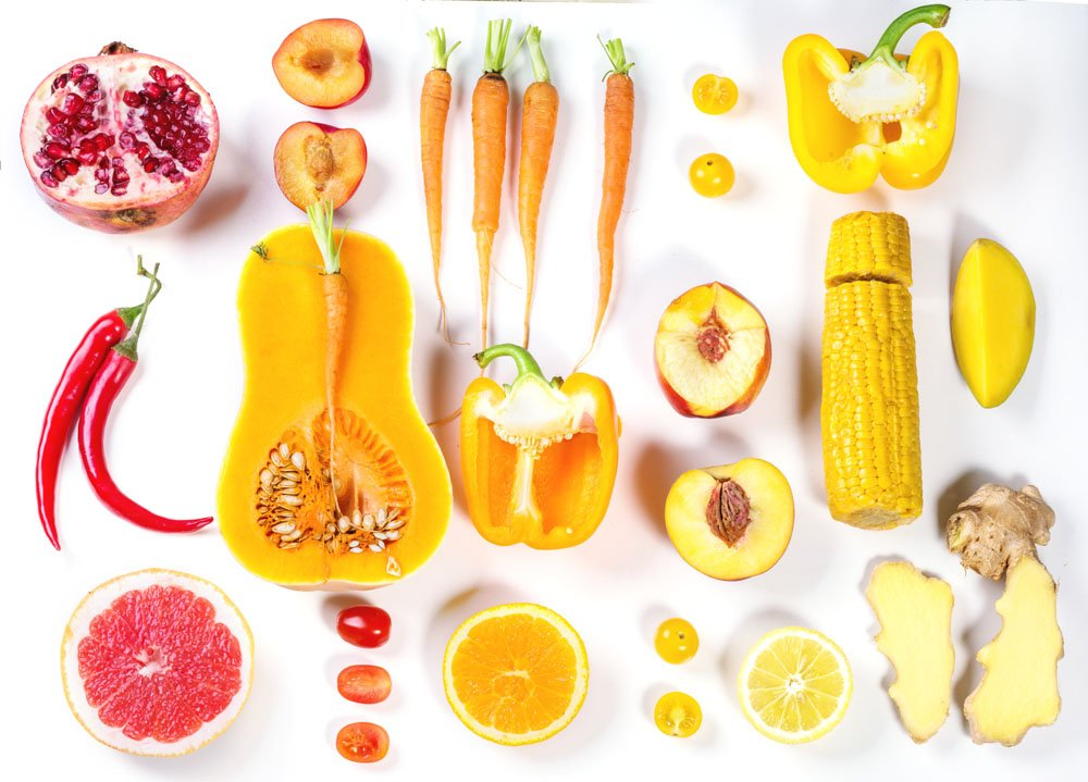 Set of whole and sliced red, orange and yellow vegetables over white background. Top view