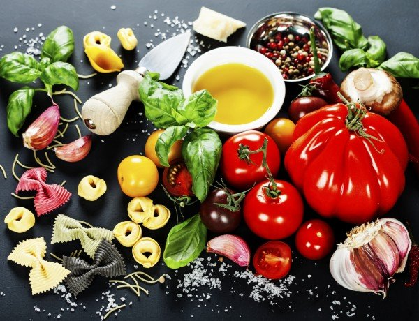 mediterranean diet ingredients: garlic, tomatoes, oil, pasta, basil, olives, herbs
