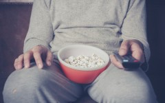 couch potato: Young man is sitting on a sofa and eating popcorn while watching television