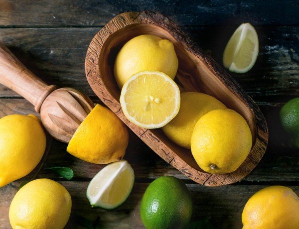 Heap of whole and sliced lemons and limes in olive wood bowl and citrus reamer over wooden background. Top view