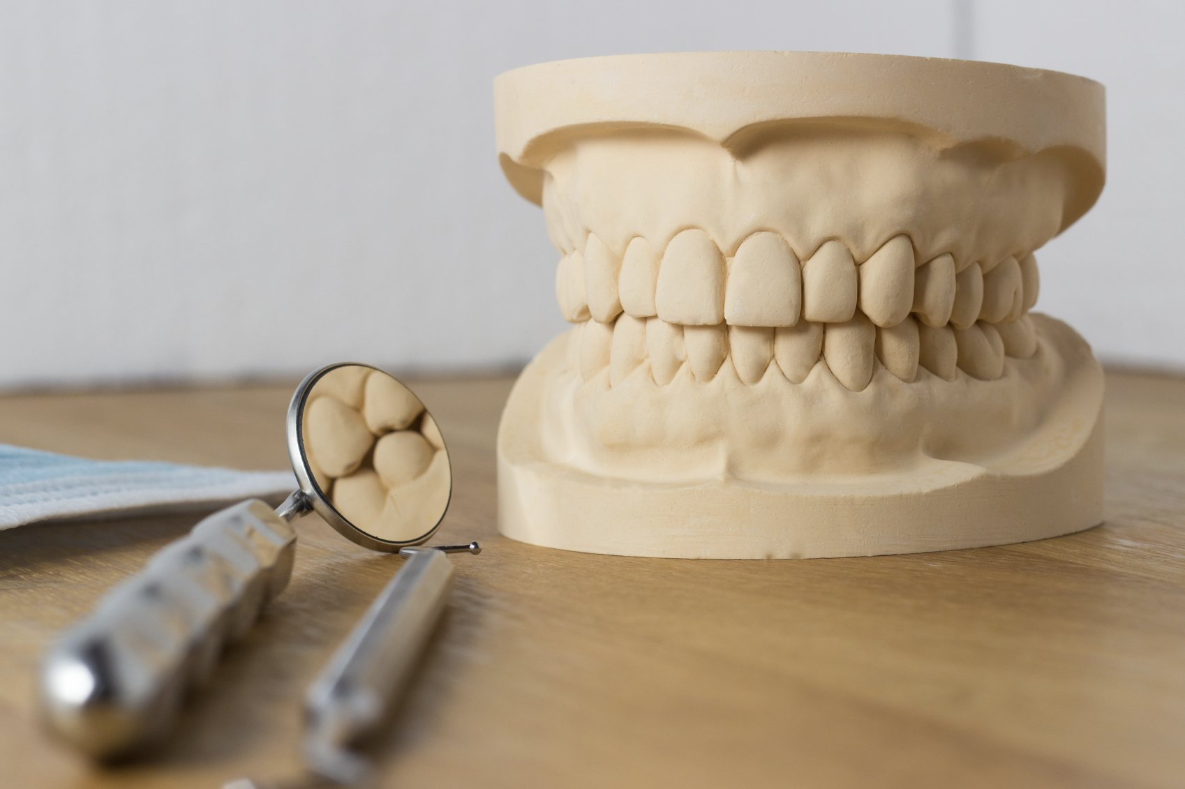 Dental mold of a set of false teeth with dental tools on a wooden table arranged so that the mirror reflects the teeth in a dentistry and healthcare concept