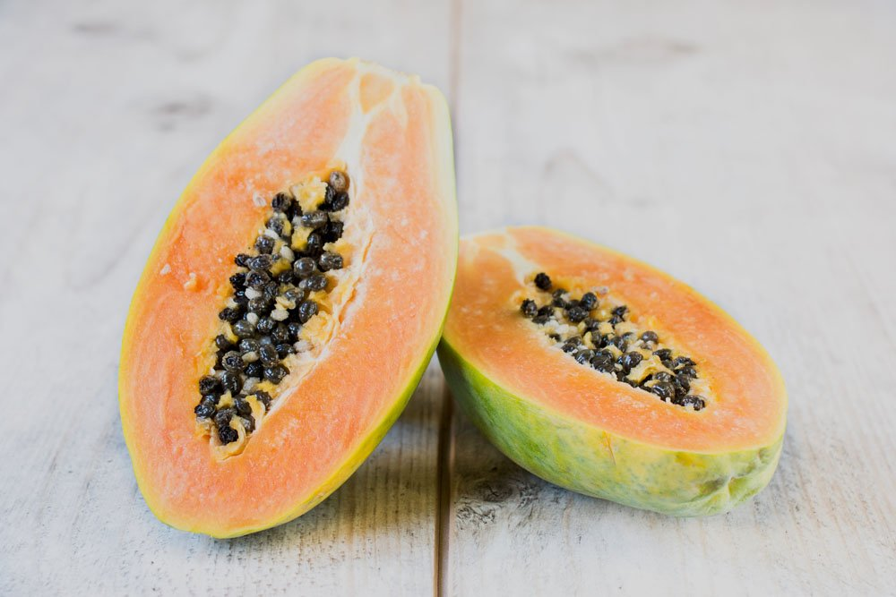 Sliced papaya fruit on wooden table,selective focus