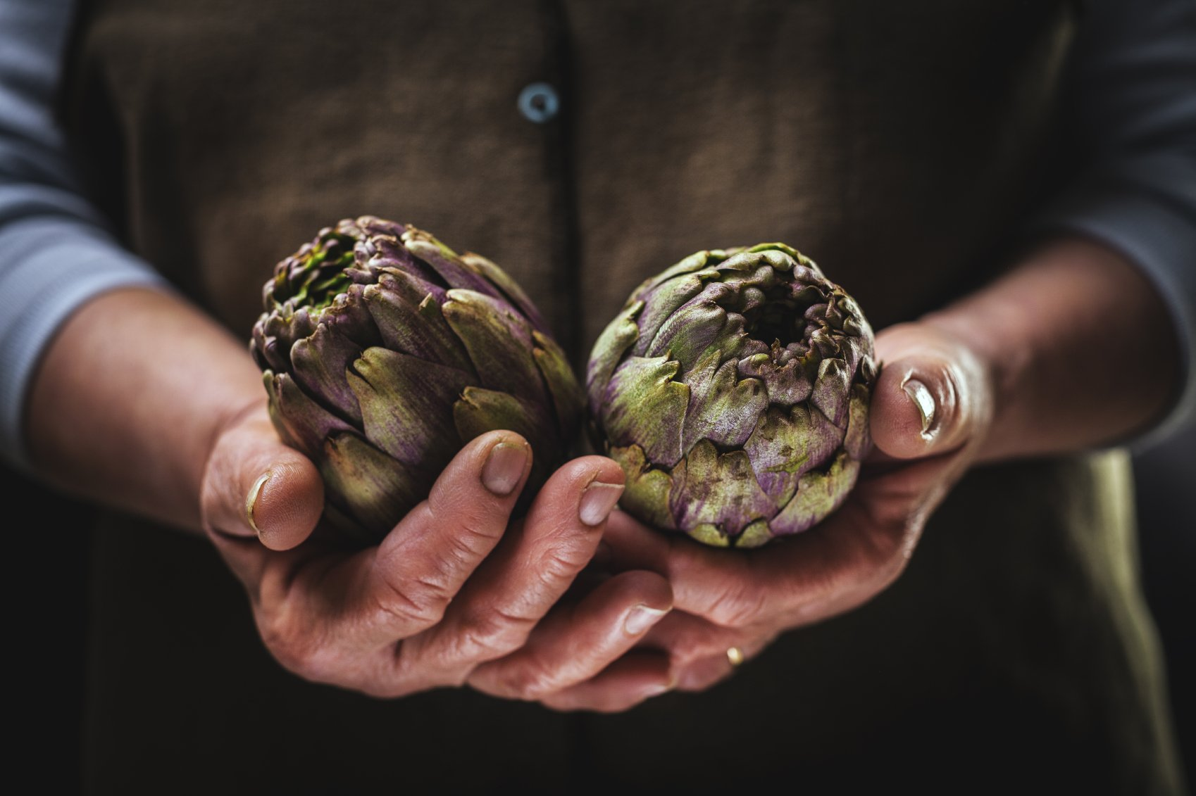 a woman holds two artichokes in her hands
