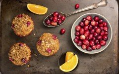 Freshly baked cranberry muffins on a rustic baking pan with cranberries and orange slices.