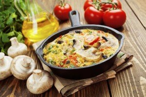 Frittata in a frying pan with mushrooms and peppers