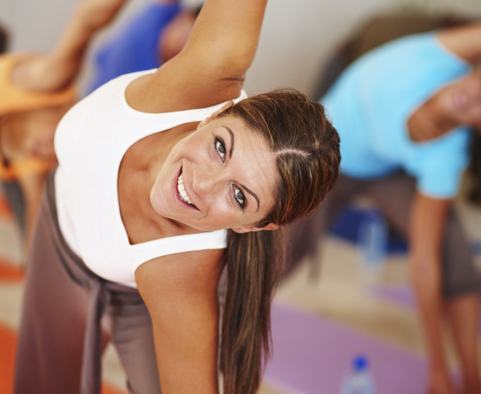 Close up portrait of an attractive woman stretching sideways and smiling at the camera during pilates class