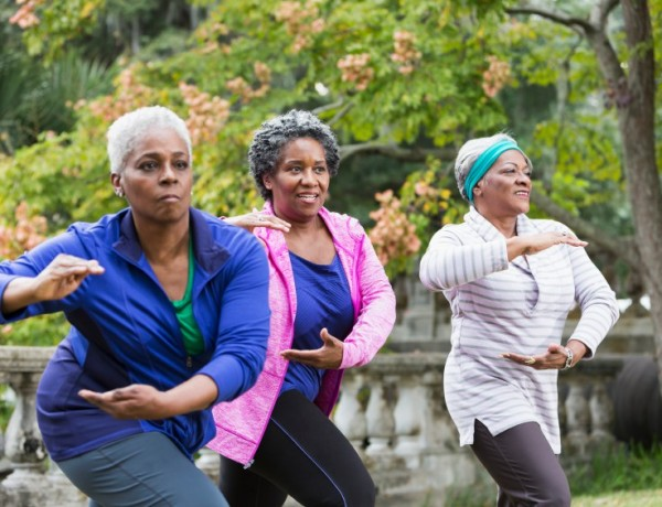 Three senior African American women at the park doing Tai Chi exercises. The woman on the left is out of focus.