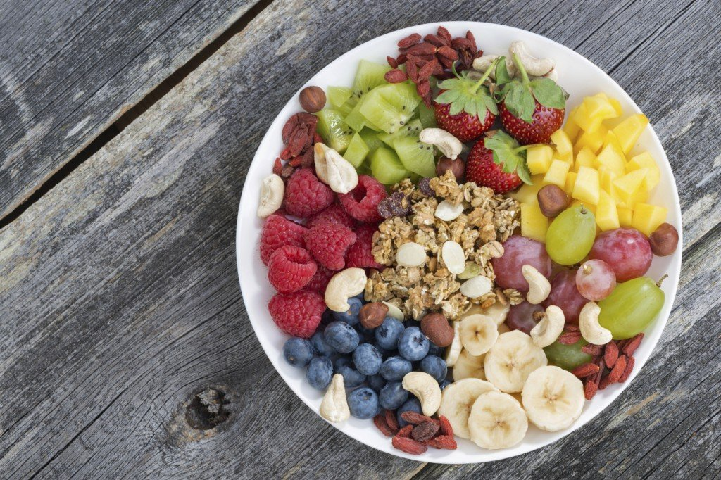 fiber rich foods including fruit, nuts and granola in a white bowl on wood table