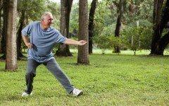 Senior man (60s) exercising in park, practicing tai chi.