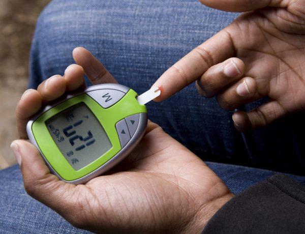 African American Woman Tests Blood Sugar. Blood sugar is slightly high.