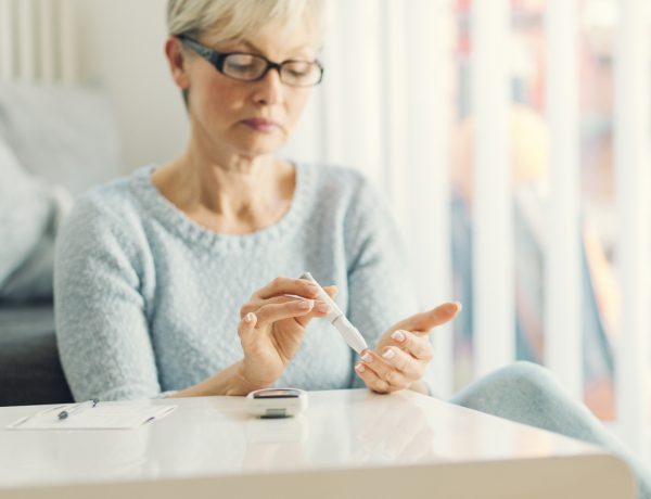 Mature woman doing blood sugar test at home in a living room. Selective focus to her finger.
