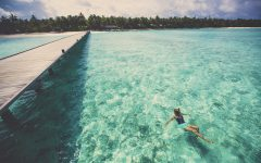 Photo of young woman swimming next to the main entrance of one of the tropical islands of Maldives