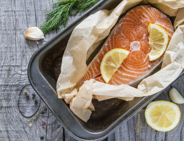 Salmon steak with pepper, dill, lemon, garlic on baking paper in baking form, rustic wood background, top view