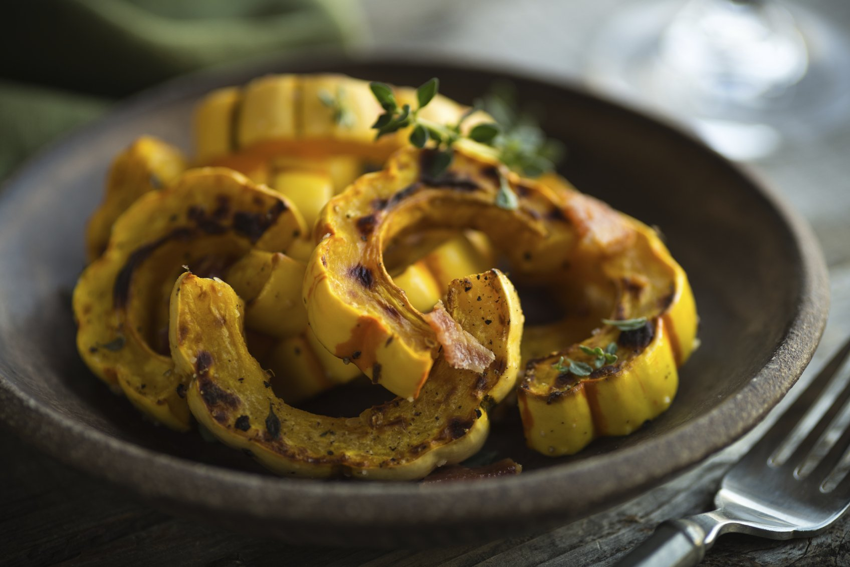 Plate with freshly roasted delicata squash and herbs